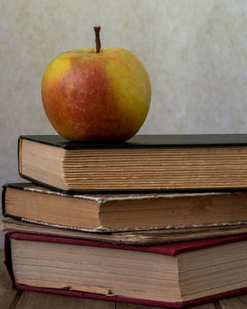 A wrinkled apple over classical books on wooden desk against brown background, viewed from the side, to illustrate the concept of outtraded or vintage learning