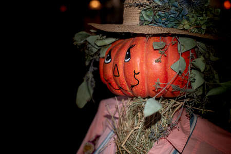 A spooky defiant jack-o-lantern scarecrow wearing a straw hat and pink clothes, halloween decoration, portrait, viewed from the side