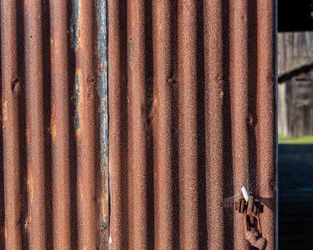 Rusty metal door with corrugated, wavy pattern, background and texture