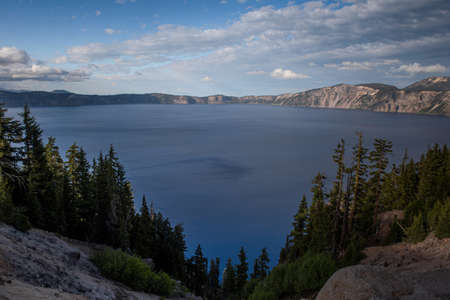 Panoramic view of the blue Crater Lake from the Rim Village in the summer during the day, against blue sky with clouds, featuing reflections in the water