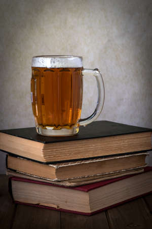 A glass of golden beer over a stack of hardbound books on a wooden table against grey background, side view