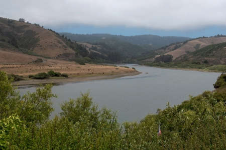Landscape view of the Russian River near its mouth  on a partly overcast, hazy day, featuring an American flag amidst the green vegetation, near Duncans Mills, California, USA