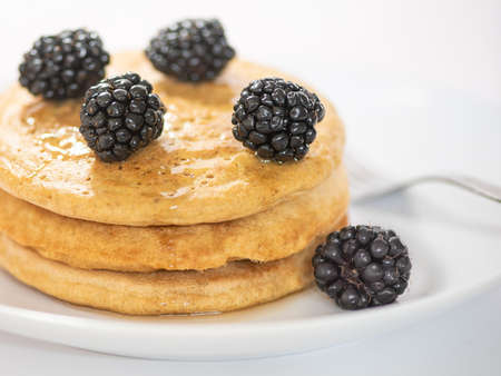 A stack of three pancakes on white plate and table, viewed from the side, garnished with blackberries, and a fork silverwear, selective focus, cropped
