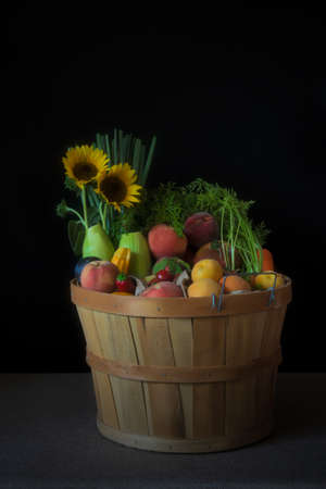 Basket with assorted fruit and vegetables against black background, side view, and decorated with sunflowers, summer harvest concept, California crop