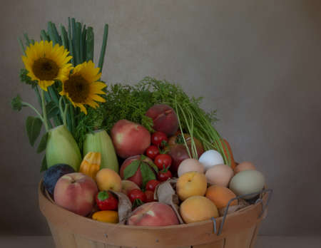 Top of basket with assorted fruit and vegetables against brown background, side view, and decorated with sunflowers, summer harvest concept, California crop