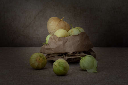 Close-up on a group of tomatillos on brown paper, stacked, with copy-space, side view