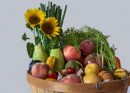 Top of basket with assorted fruit and vegetables against white background, side view, and decorated with sunflowers, summer harvest concept, California crop