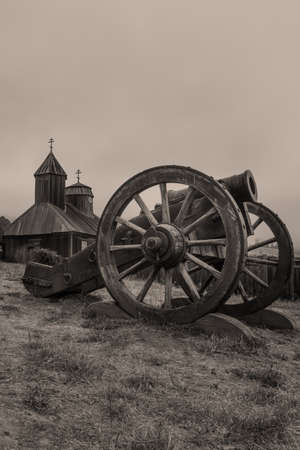 Old Fort Ross canon and church, State Park, California, USA, on a overcast day, aged photograph, sepia tone 新闻类图片