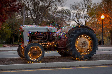 Winters, California, USA, Dec 6, 2019. Christmas. Rural town old, vintage Ford tractor decorated with Christmas lights