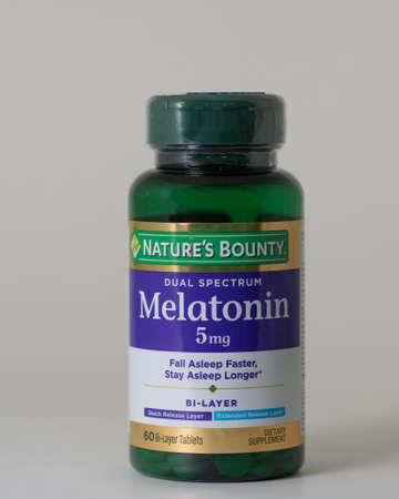 Davis, CA, August 3, 2020. A bottle of Natures Bounty Dual Spectrum Melatonin 5 mg on whit background. Melatonin is a natural hormone that regulates the sleep–wake cycle.