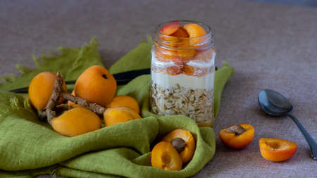Loquats and overnight oats on brown table and green tablecloth, swith copy-space, viewed from an agle- healthy eating concept