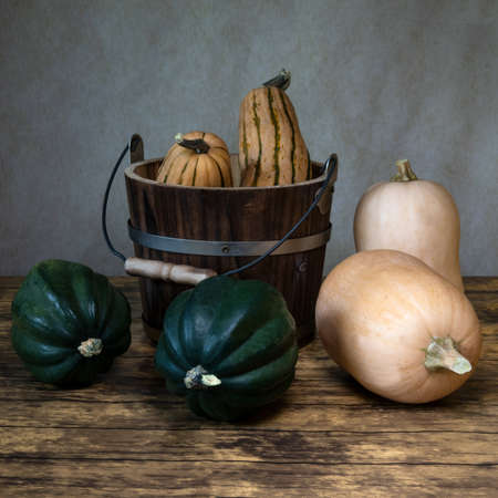 Three types of winter squash, Delicata Squash, acorn squash and butternut squash and a bucket, viewed from the side, on wooden table, whole fruit, still life display
