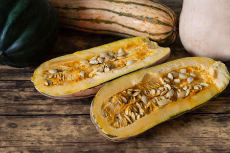 Three types of winter squash, Delicata Squash, acorn squash and butternut squash, the delicata squash is cut in half, viewed from an angle, on wooden table