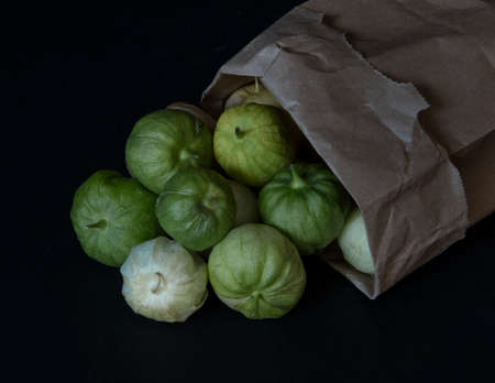 Tomatillos spilling from a paper bag that is turned over, on black background- California produce concept Stockfoto - 157151118