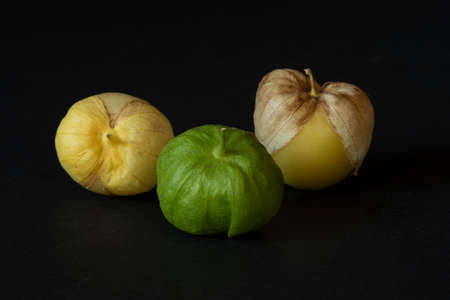 Unwashed Yellow and green tomatillos  on black background, viewed from dinner angle- California produce concept Stockfoto