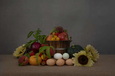 Still life portraying California crops harvested in the summer, eggs and decorated with sunflowers, on brown background, side view with copy-space