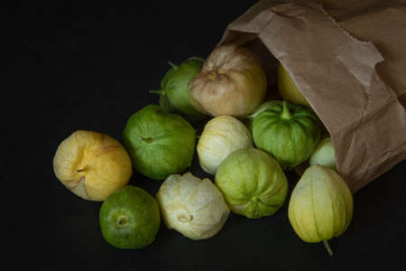 Tomatillos spilling from a paper bag that is turned over, on black background, viewed from dinner angle- California produce concept Stockfoto