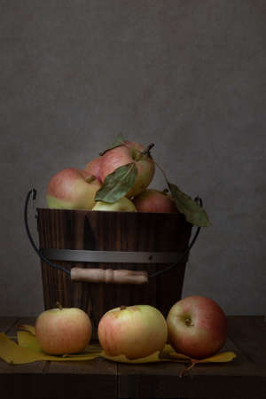 Honey Crisp apples  from Apple Hills, Northern California, inside a wooden bucket on wooden table covered with yellow cottonwood leaves against brown background and viewed from the side Stockfoto