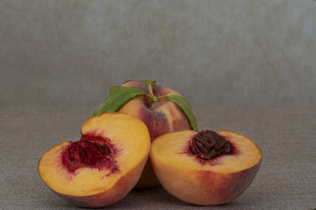 Two fresh yellow peaches on brown table, one whole and one cut in half, centered, with macro detail , side view- harvest still life, with plenty of copy-space Stockfoto