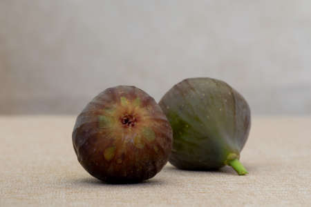 Two brown turkey figs side-by-side on tan background viewed from the side high angle view with plenty of copy-space