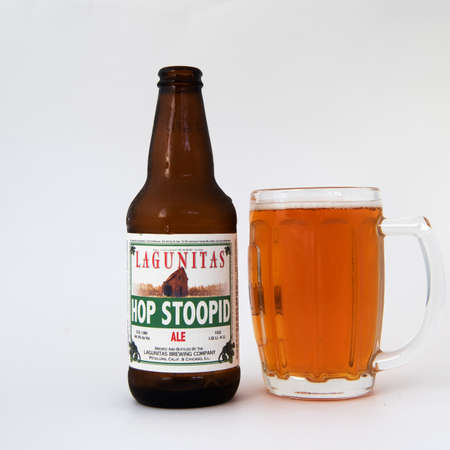 Davis, CA.  August 16, 2020: An open bottle of Lagunitas hoppy beer  isolated against a white background, and served in a beer glass