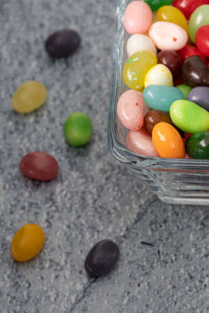 Jelly beans on blue background,  festive and colorful composition with candie, macro detail shot top view Stockfoto