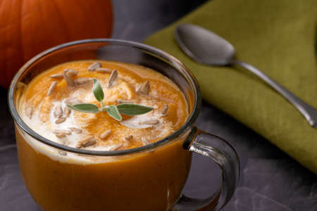 Pumpkin soup in transparent bowl, close-up and angle view, decorated with sage leaves and sunflower seeds, beside a green napkin and a spoon- seasonal dish to warm the soul Stockfoto