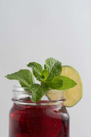 Top of the cup  of red, medicinal hibiscus tea in transparent glass on white background, garnished with green slices of lime and fresh mint. Stockfoto