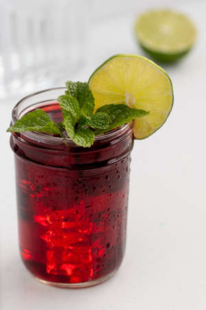 Transparent glass cup of medicinal hibiscus tea in on white background, garnished with slices of lime and fresh mint, home Apoteke concept Stockfoto
