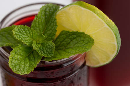Top of cup  of medicinal hibiscus tea and dried hybiscus leaves in transparent glass on white background, garnished with slices of lime and fresh mint.