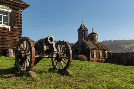 near Salt Point, 19 January 2021. Old Building, church and canon at Fort Ross state park, a Russian Fort, on a sunny day, California, USA