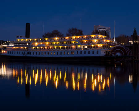 Sacramento, CA, Dec 19 2020. Old Sacramento Delta King Hotel at night viewed from West Sacramento across the river, featuring light reflections Redactioneel