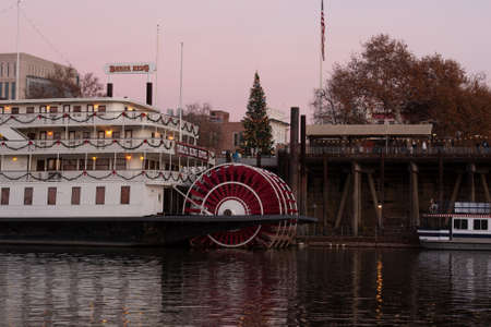 Sacramento, CA, Dec 19 2020. Old Sacramento with christmas tree viewed from West Sacramento across the river, featuring part of the Delta King Hotel, in the sunset