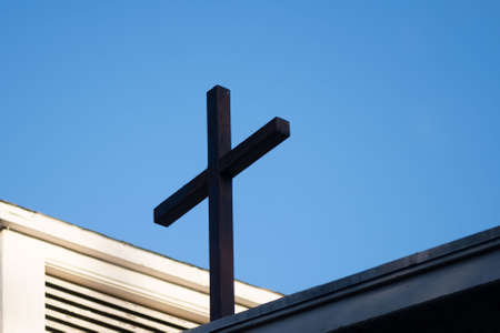 Cross on top of a church against the blue sky with copy-space, religious concept and background