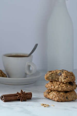 Oatmeal Cookies ion white background and decorated with spices and served with a cup of coffee and milk, side view