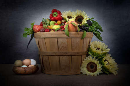 California mid-summer produce and eggs in basket against grey background and decorated with sunflowers, side videw Stockfoto