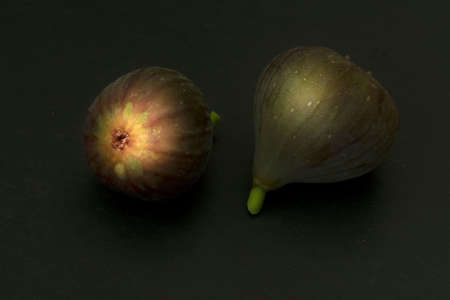 Two brown turkey figs side-by-side on dark background viewed from the side high angle view with copy-space