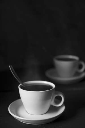 Two cups of espresso on black background, still life with caffeinated drinks, dark and moody with lots of copy-space