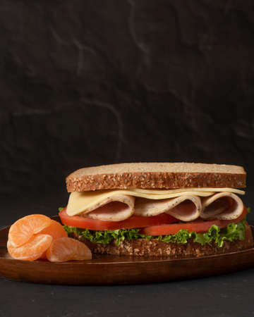One healthy sandwich made with whole wheat bread, lettuce, tomato, turkey and cheese on wooden plate on black background, served with tangerine buds, side view, vertical Stockfoto