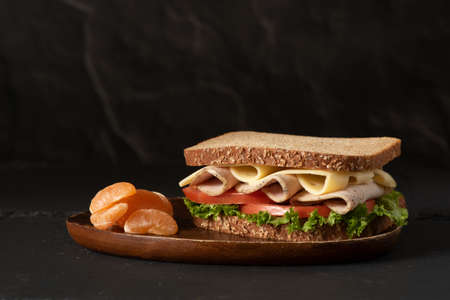 One healthy sandwich made with whole wheat bread, lettuce, tomato, turkey and cheese on wooden plate on black background, served with tangerine buds, side view, horizontal