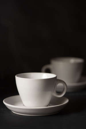 Two empty espresso cups viewed from the side against black background