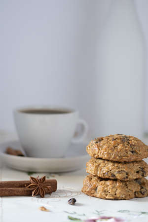Oatmeal and Raisins Cookies  on white background and decorated with spices, served with coffee and a jar of milk in the back, side view Stockfoto