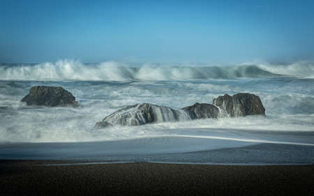 Waves coming towards the beach, long exposure on a blue sky day with no clouds, and lots of copy-space, Schoolhouse Beach in Sonoma County, CA, USA