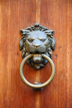 Bronze lion head knocker on a wooden door photo