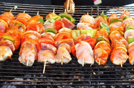 Shish kebab on skewers on hot barbecue grill photo