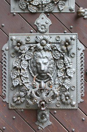 Bronze lion head knocker on a wooden door Stock Photo - 12817813
