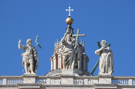 Statues of Christ, John the Baptist, and an apostle on the top of Saint Peter Basilica facade  Rome, Italy Stock Photo - 12816084