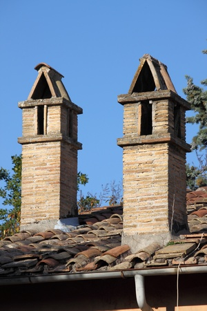 Old traditional rooftop chimneys constructed of bricks on a traditional medieval house photo