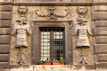 Renaissance window with flower pots and grate photo
