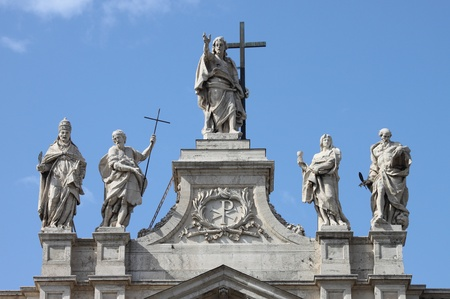 Statues of Christ and some saints on the top of Saint Peter Basilica facade. Rome, Italy Archivio Fotografico